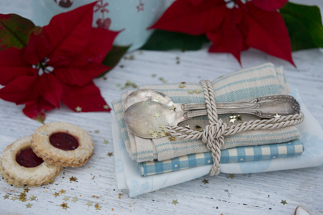 Silver spoons with napkins, jam sandwich biscuits and poinsettias