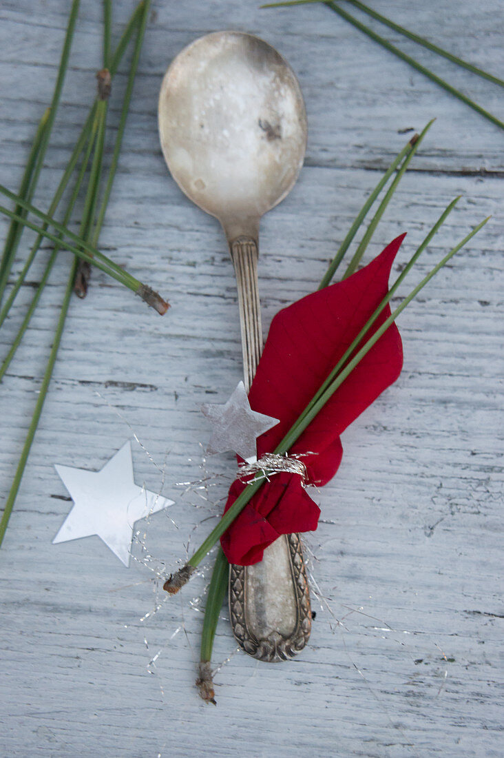 A silver spoon decorated with poinsettias and pine needles