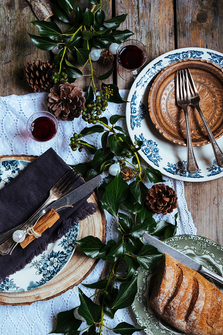 A table laid for Christmas with red wine and bread (seen from above)