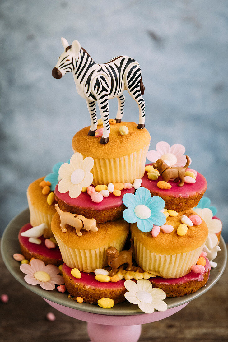 Cupcakes on a cake stand decorated with animal figures, flowers and sweets