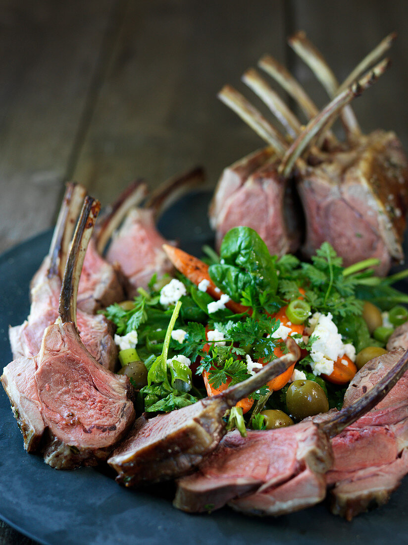 Lamb crown with a spinach and olive salad and feta cheese