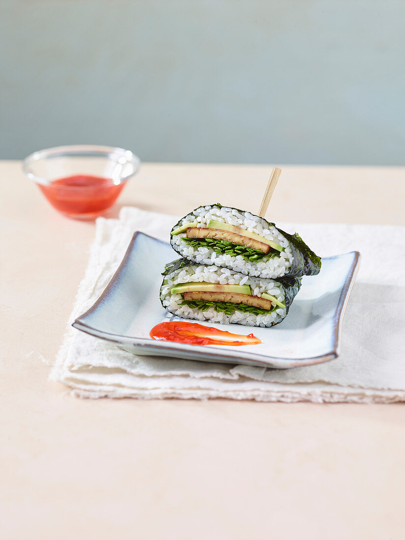 A sushi sandwich with avocado, tempeh and spinach