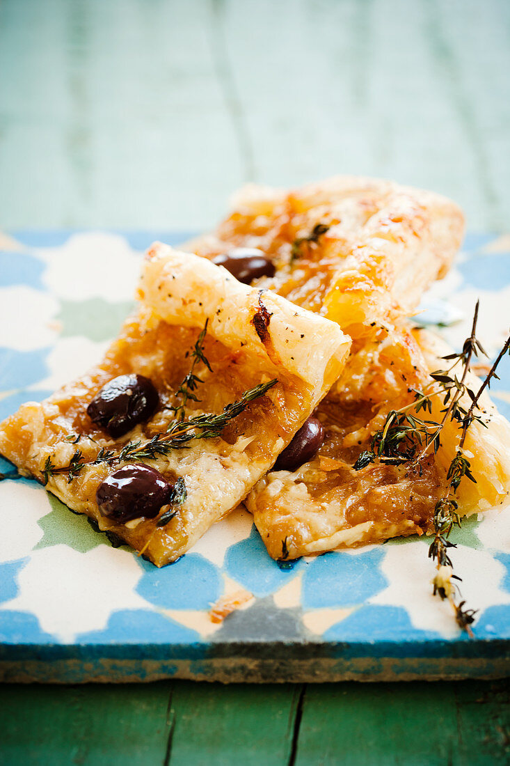 Slices of caramelised onion tart with olives and thyme