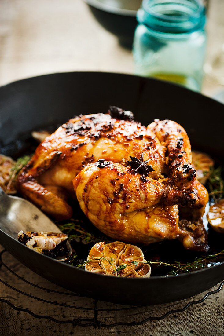 Chicken with an orange glaze, spices and garlic in a pan