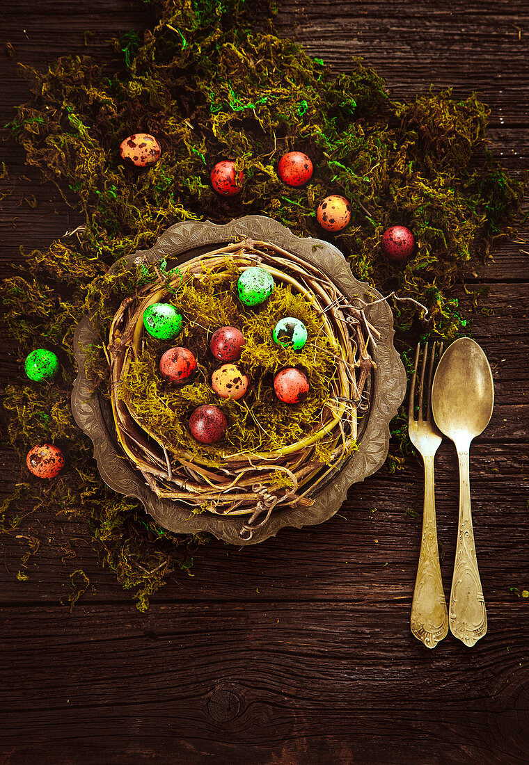 Dyed Easter eggs in an Easter nest made from twigs and moss on a wooden table (seen from above)