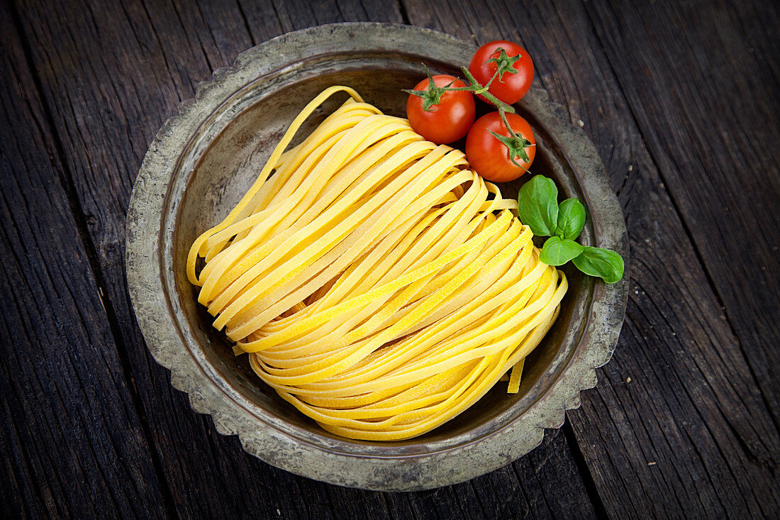 Fresh tagliatelle in a pewter bowl (seen from above)