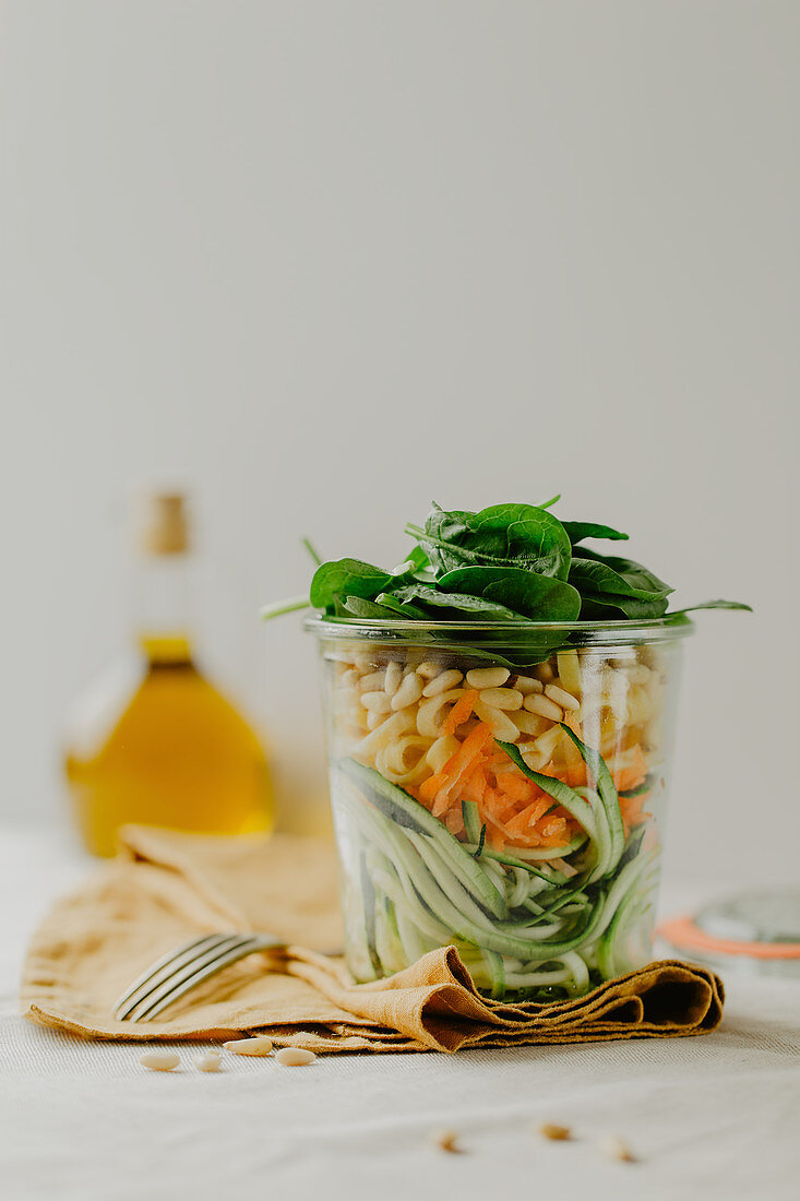 A layered salad with vegetables and a yoghurt dressing in a glass