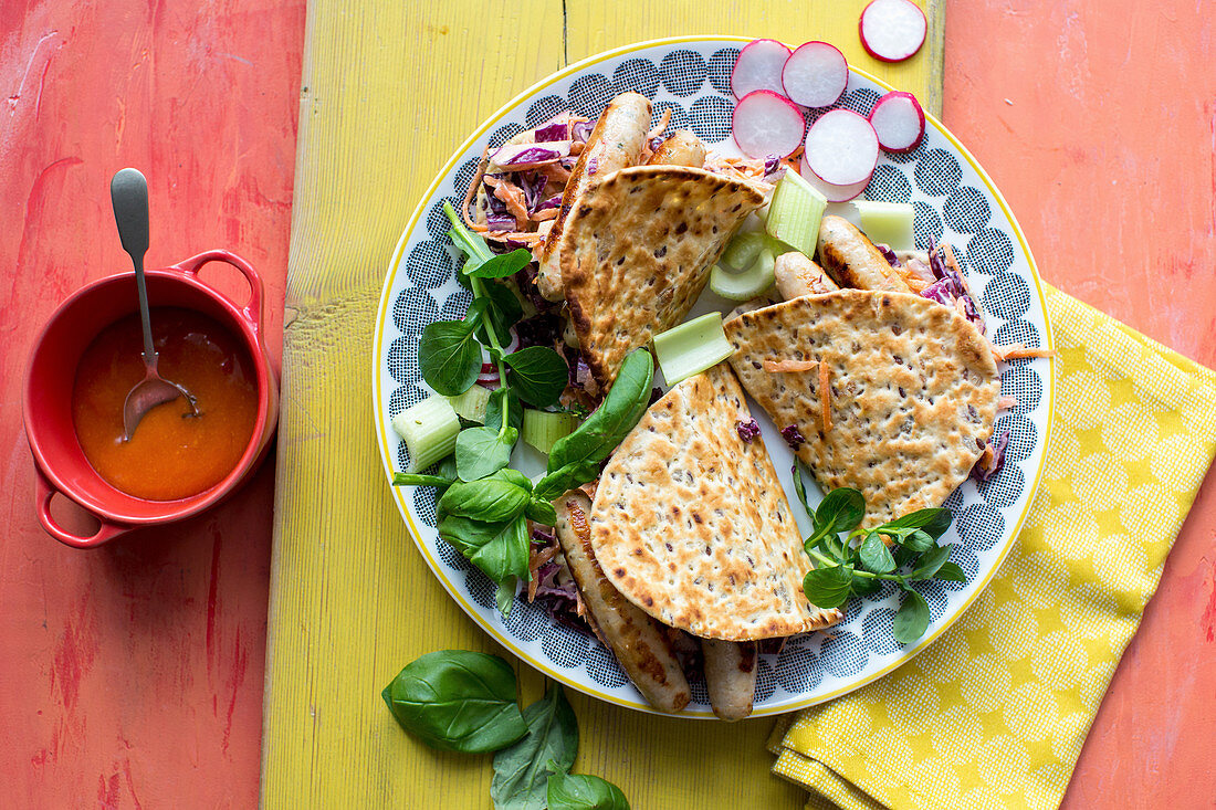 Lowfat chicken sasages in flat bread with rebcabbage slaw