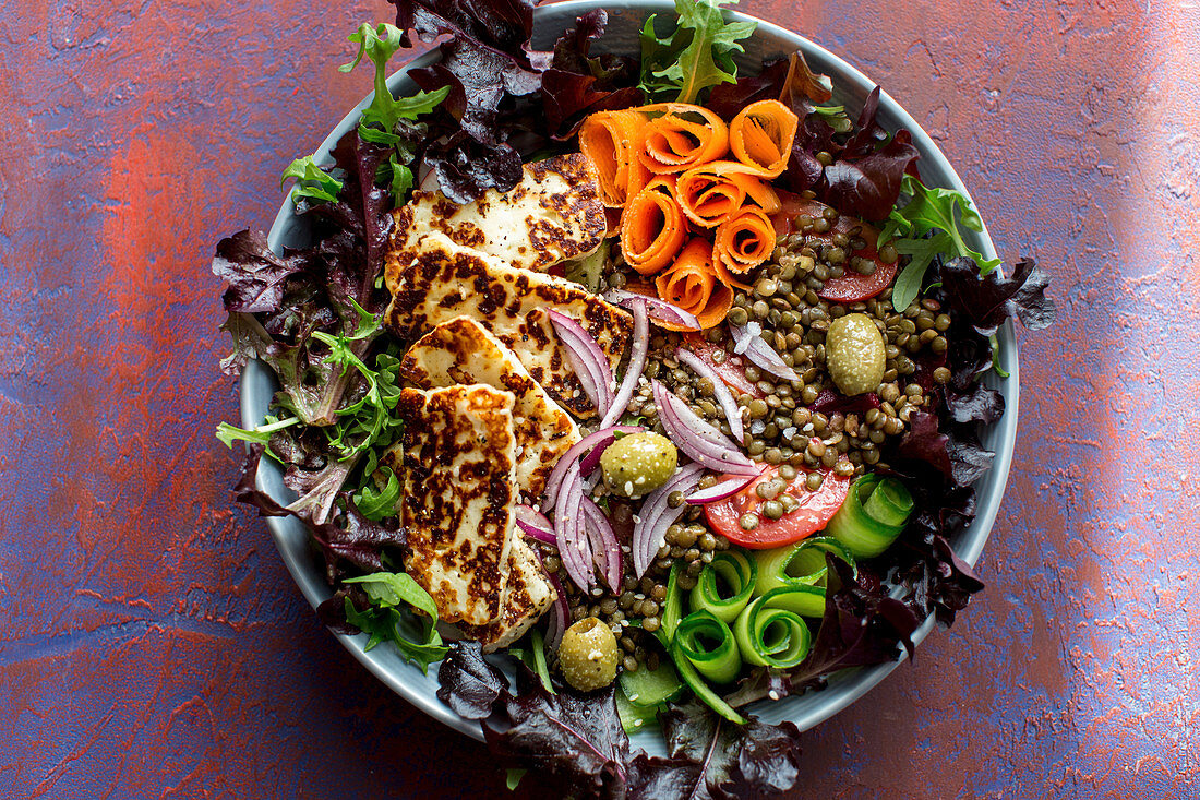 Mixed vegetable salad with carrots, cucumbers, lentils, olives, radishes, red onion, tomato and haloumi