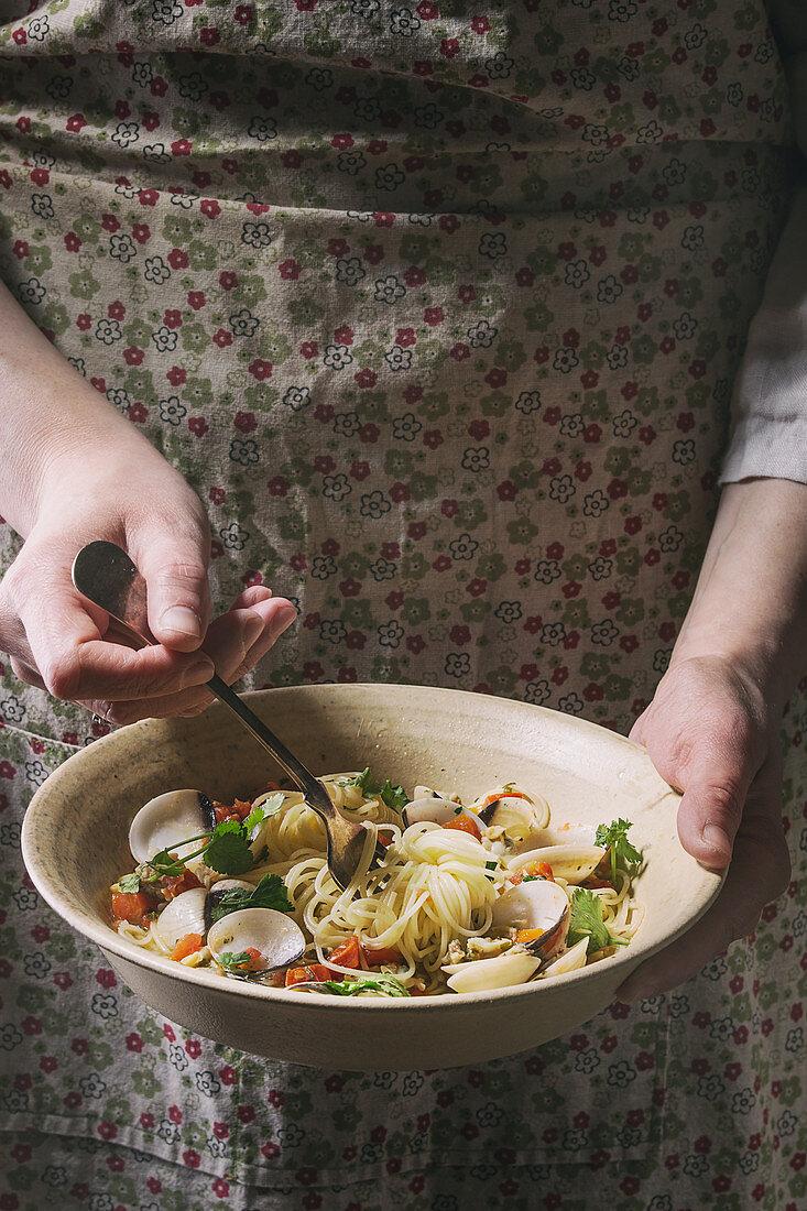 Traditional italian dish pasta spaghetti Vongole in tomato sauce in ceramic bowl in female hands
