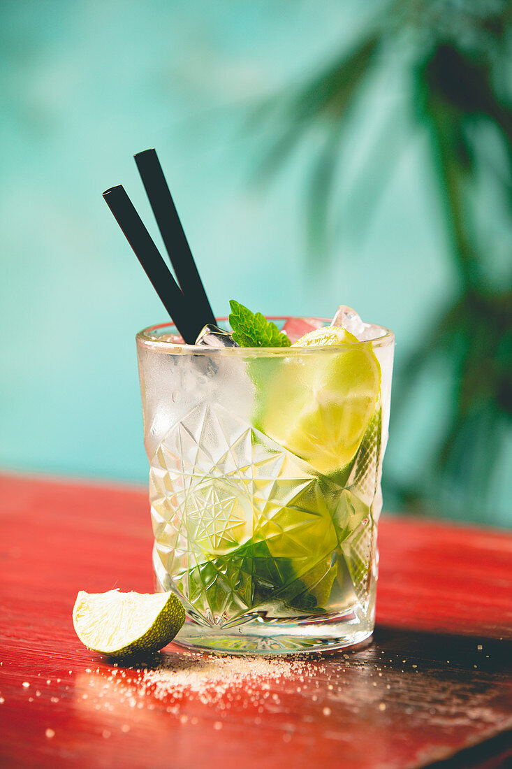 Mojito cocktail with fresh lime and mint on a wooden table