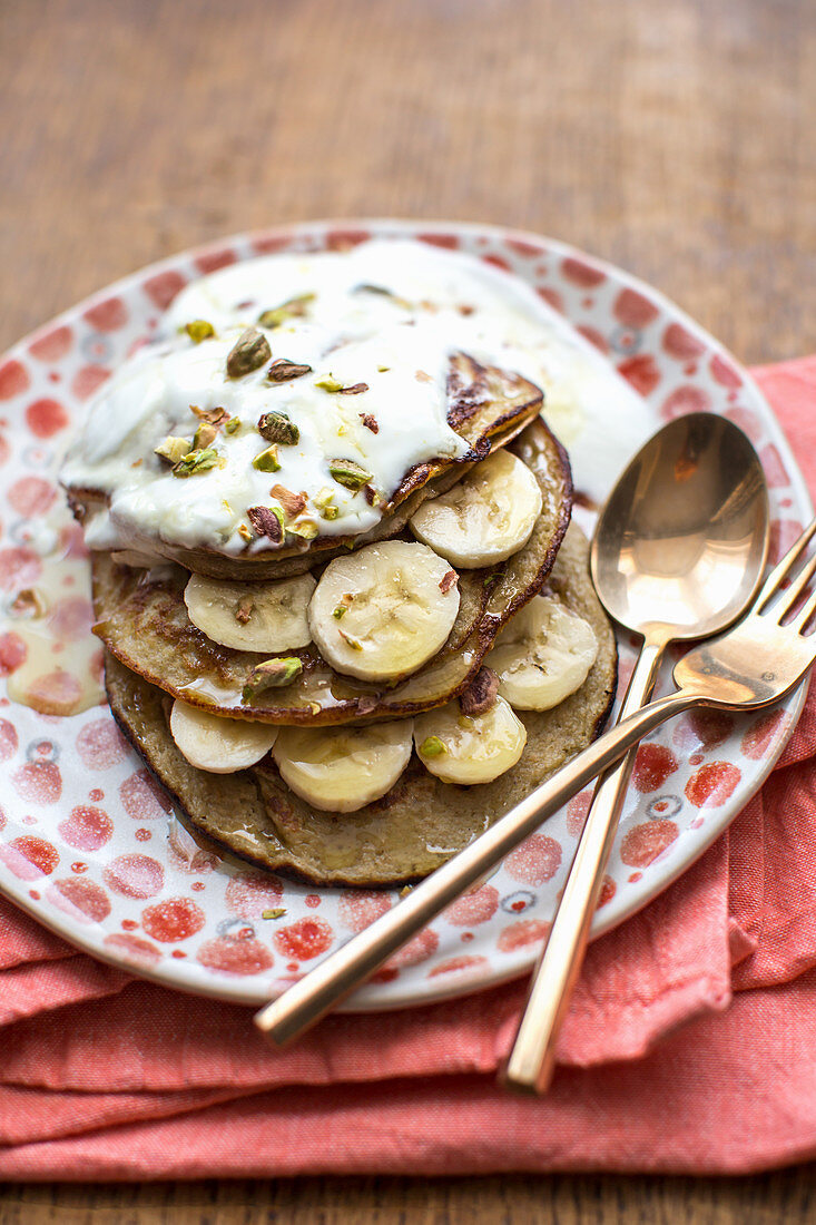 Banana pancakes made from gluten free porridge oats, banana and a free range egg topped with banana, pistachio nuts, natural yogurt and syrup