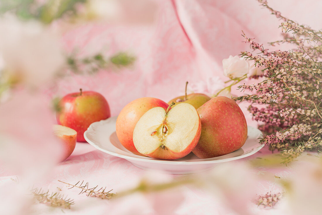Pink Lady apples on a plate, pink flowers on a pastel colored background