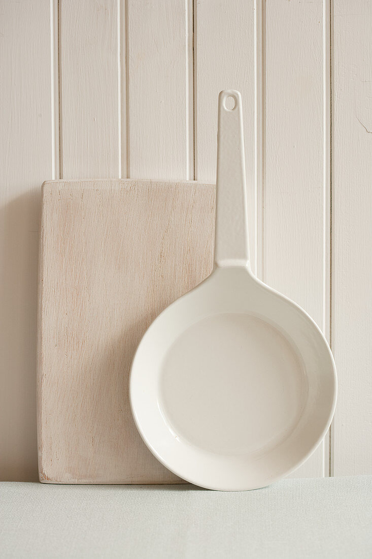 A wooden chopping board and a pan leaning against a light wooden wall
