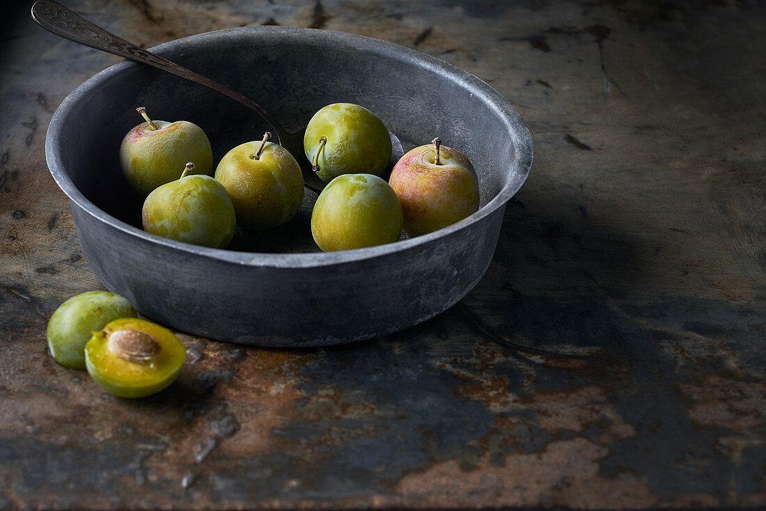 Still life of plums Reine Claude Verte on zinc background