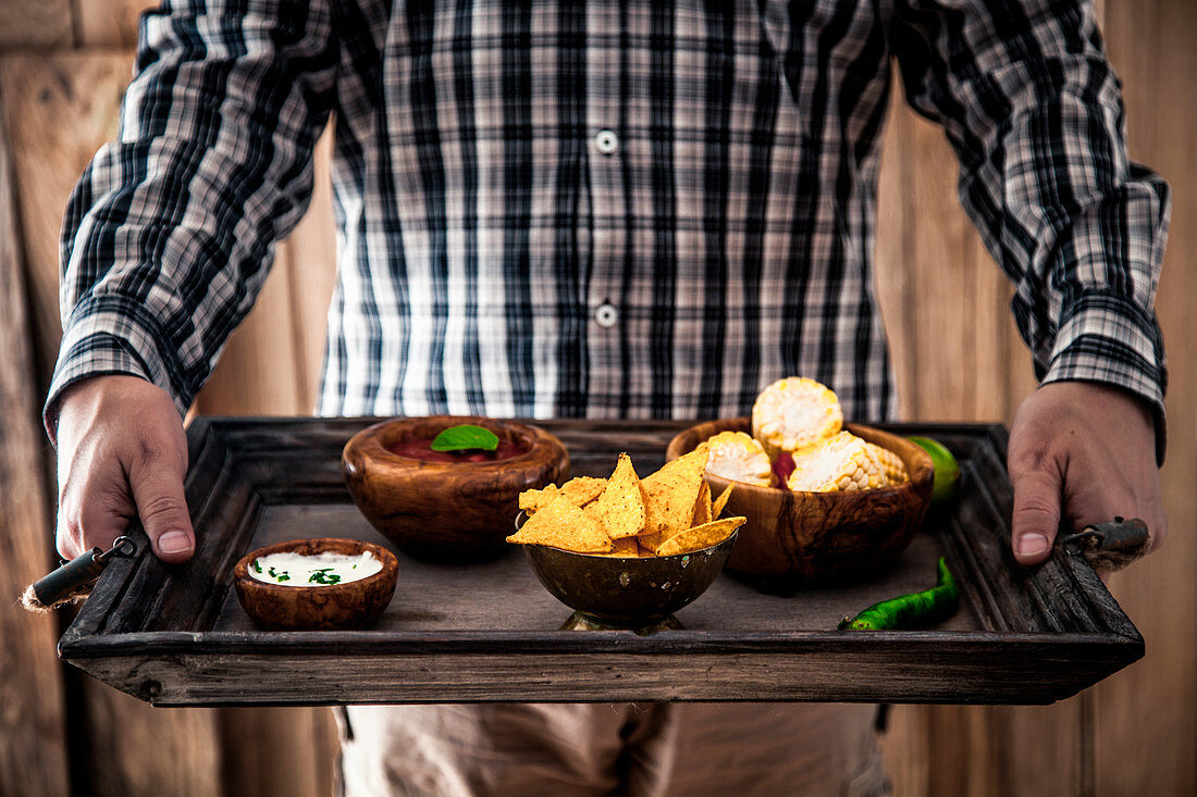 Man with snacks and dips (Mexican food)