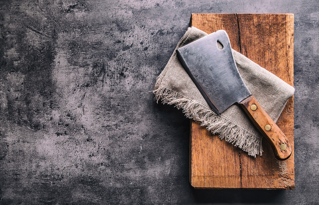 Vintage butcher meat cleavers with cloth towel on dark concrete or wooden kitchen board