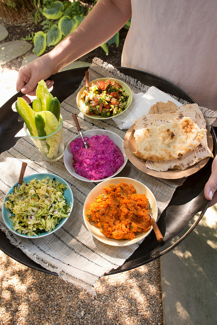 A woman serving a tray of salad, dips and flatbread in the garden