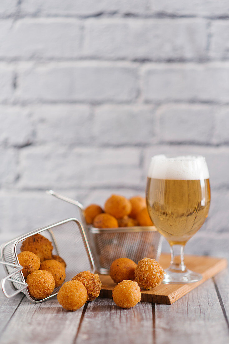 Fried cheese balls and a glass of light beer