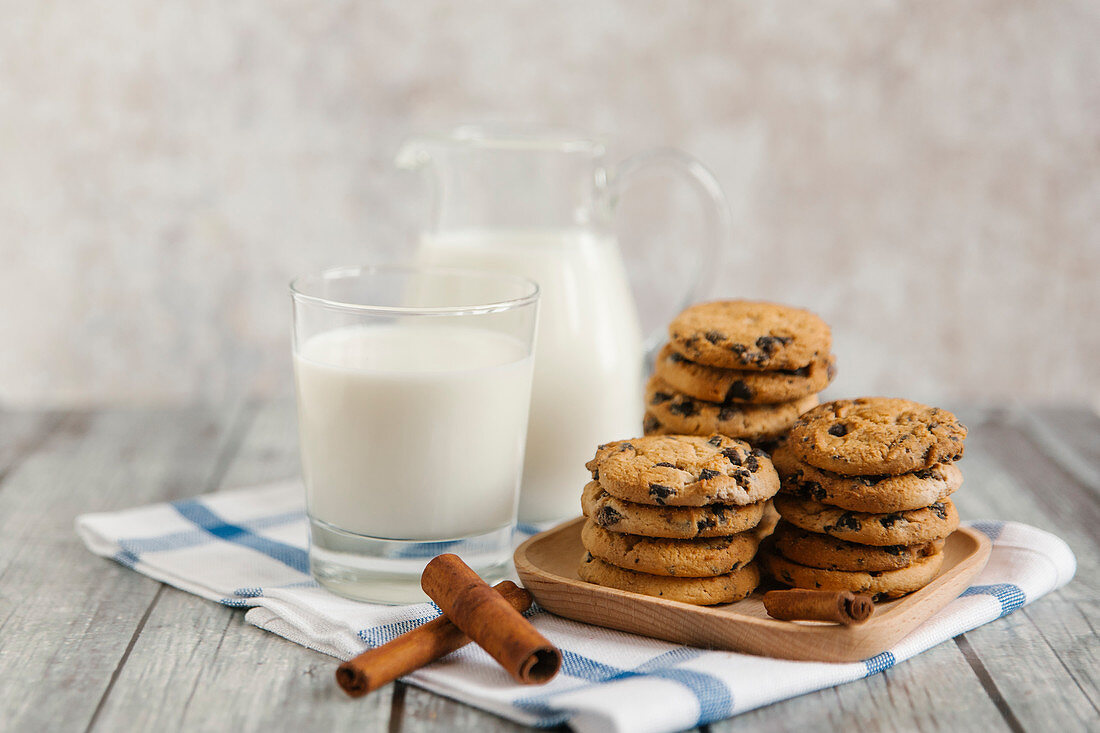 Milk in a jar and a jug, with chocolate chip cookies and cinnamon sticks