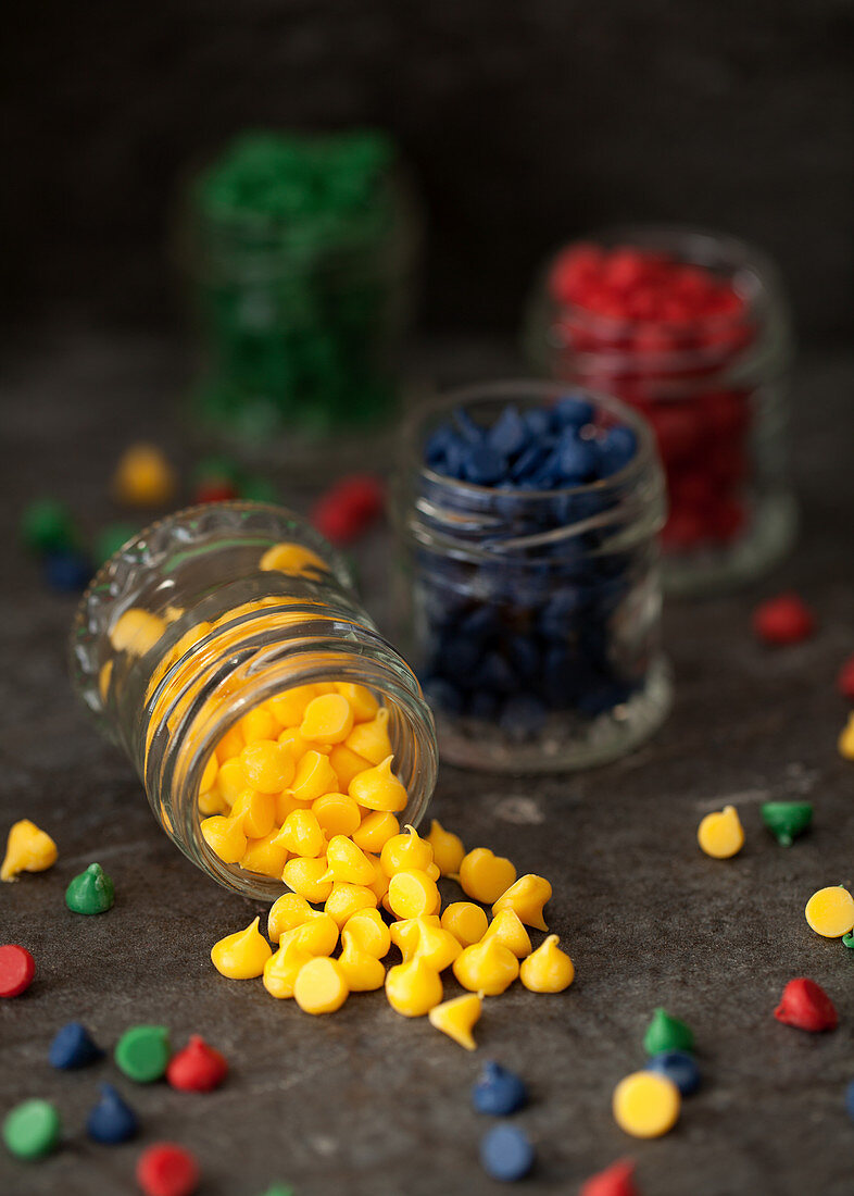 Colourful chocolate drops in glass jars