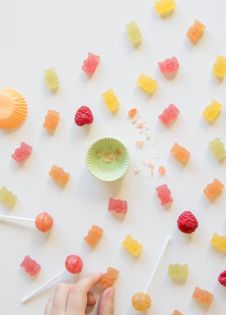 Various sweets with a child's hand