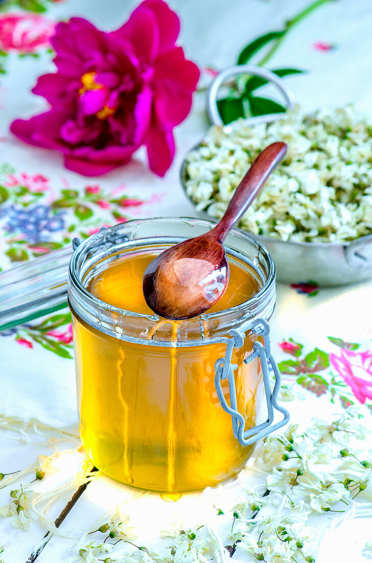 Honey in a glass jar with a wooden spoon