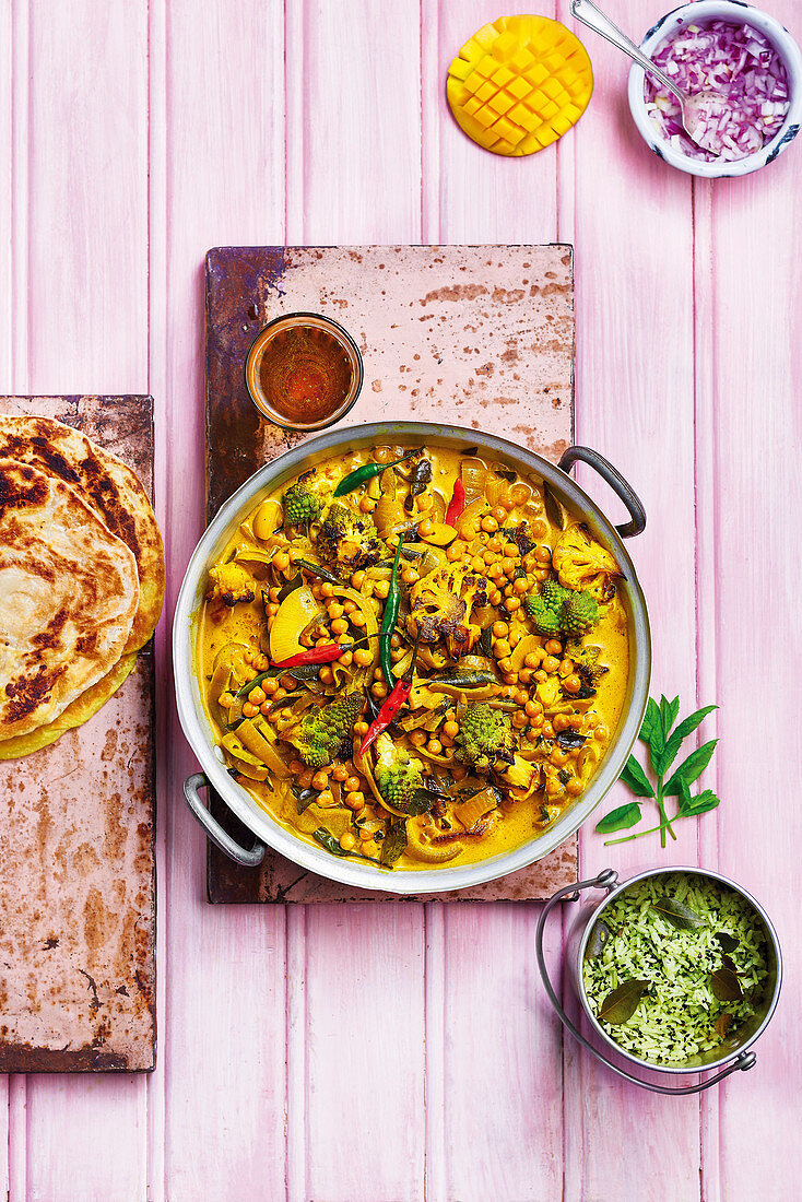 Cauliflower and Romanesco cauliflower curry with chickpeas, chilli, onions, served with rice, breads, mango and raw onion