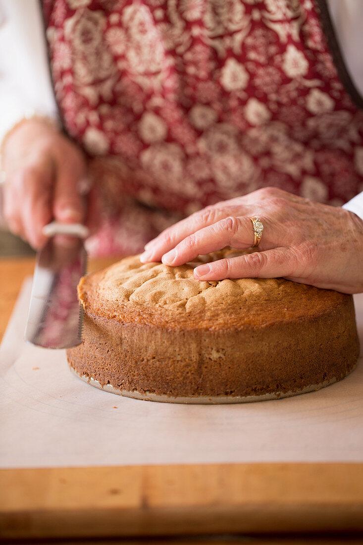 Torte zubereiten: Kuchenboden waagerecht mit Messer durchschneiden