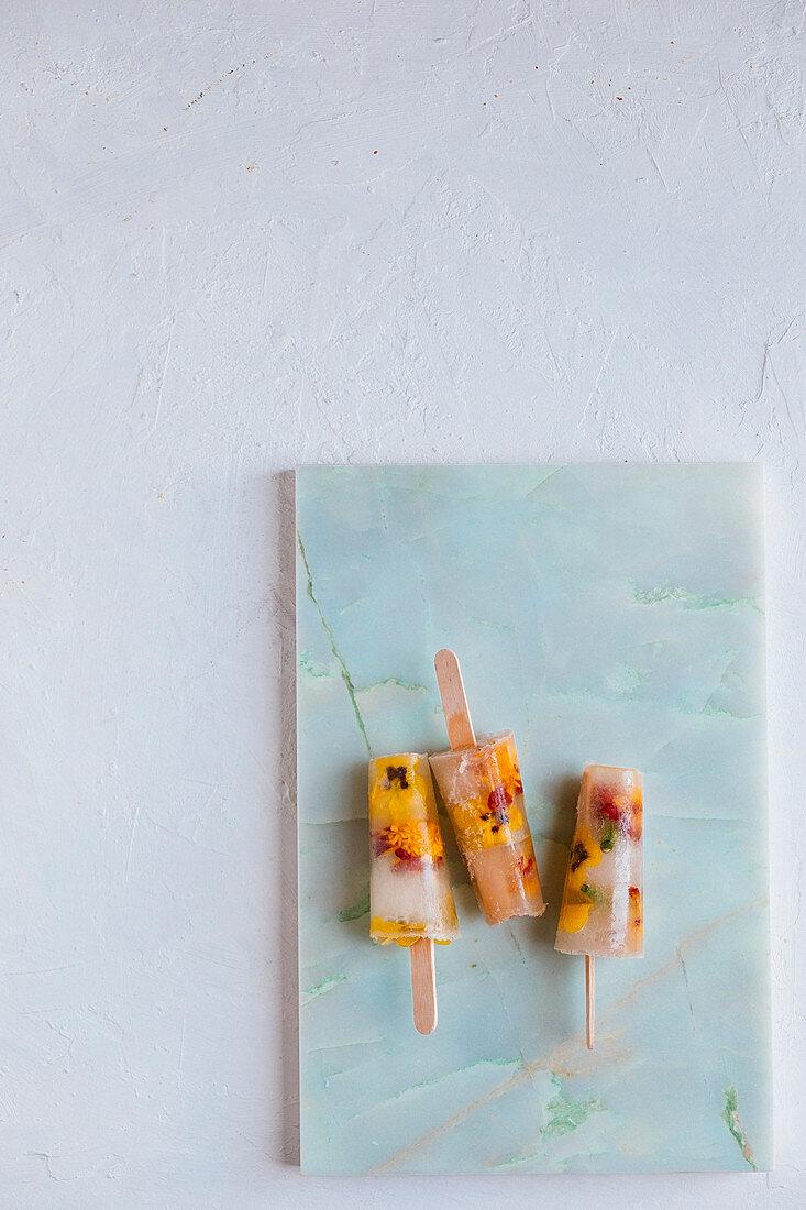 Wassereis mit Holunderblütensirup und Essblüten auf Marmorplatte