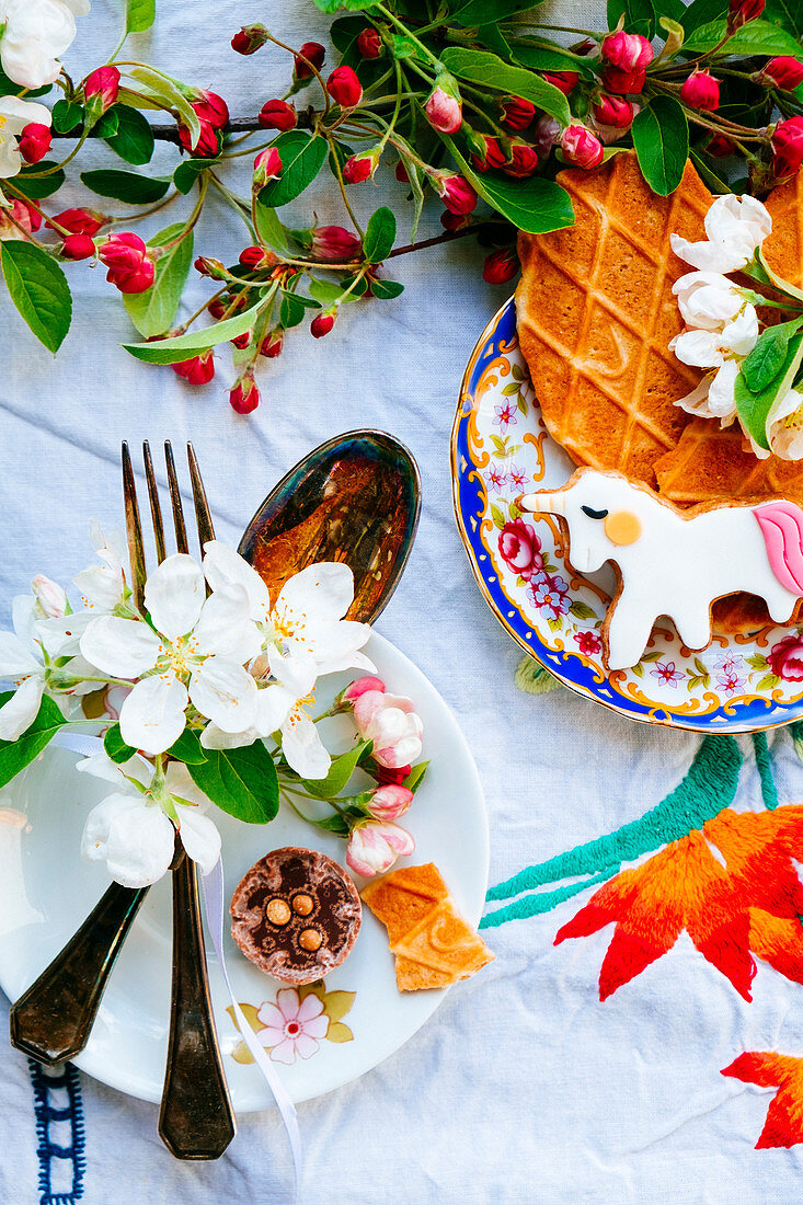Cutlery with blossom, cookies, chocolate and an unicorn cookie