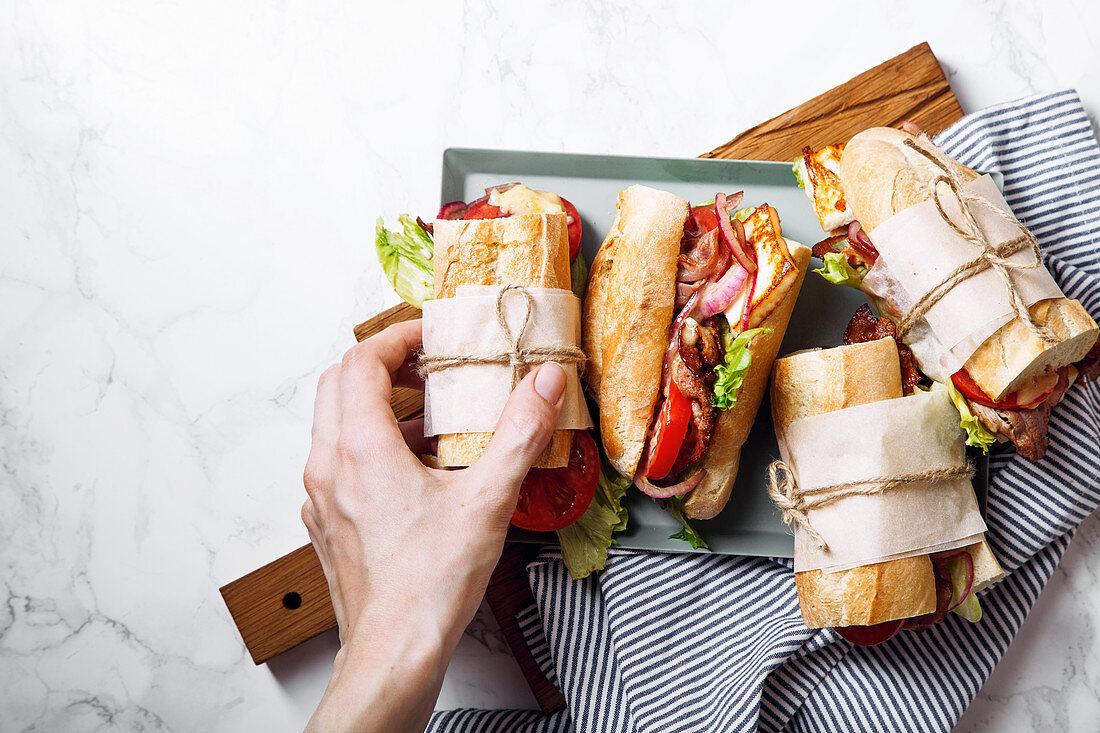Banh-Mi-Baguettesandwich mit Bacon, Käse, Tomaten und Salat