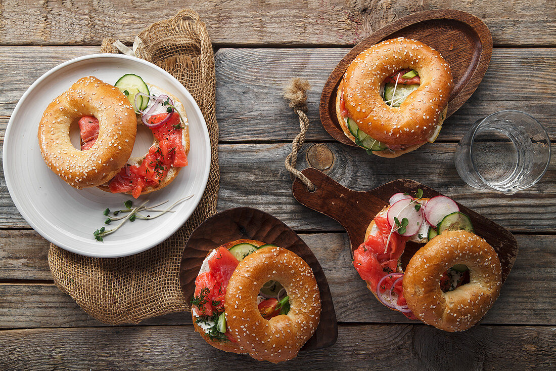 Bagels with salmon fish, cream cheese, cucumber and fresh radish slices on rustic gray wooden background