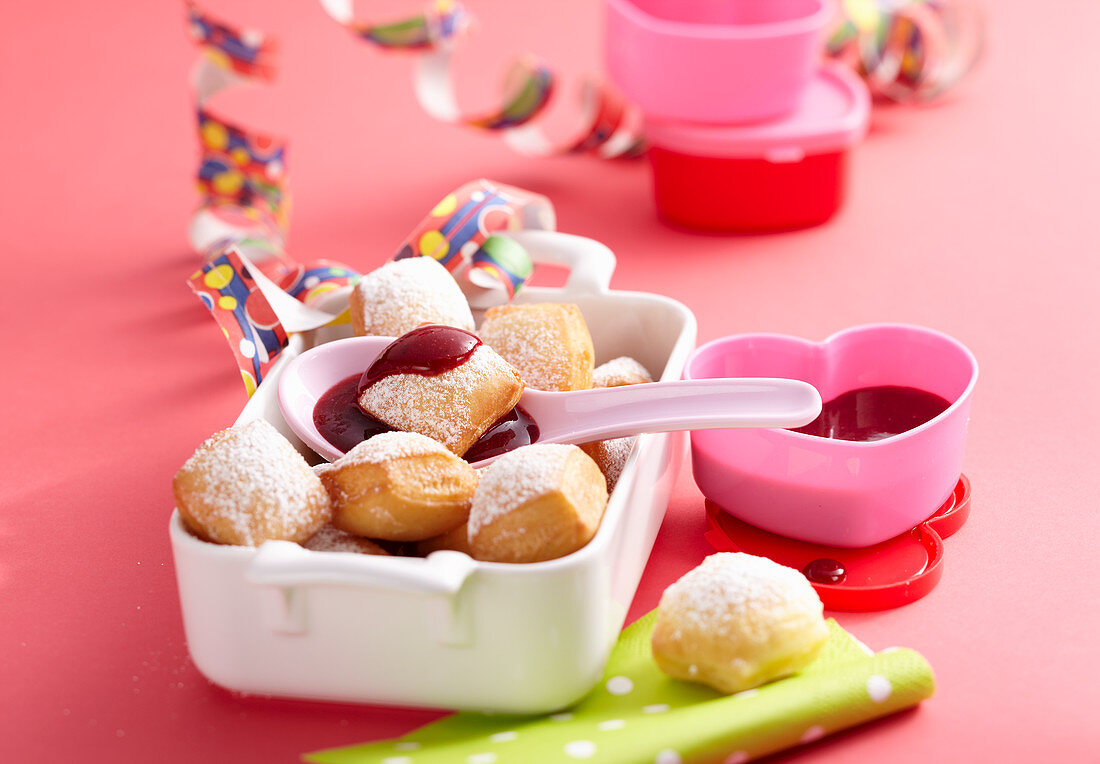Deep-fried, sweet dough cubes with lingonberry sauce