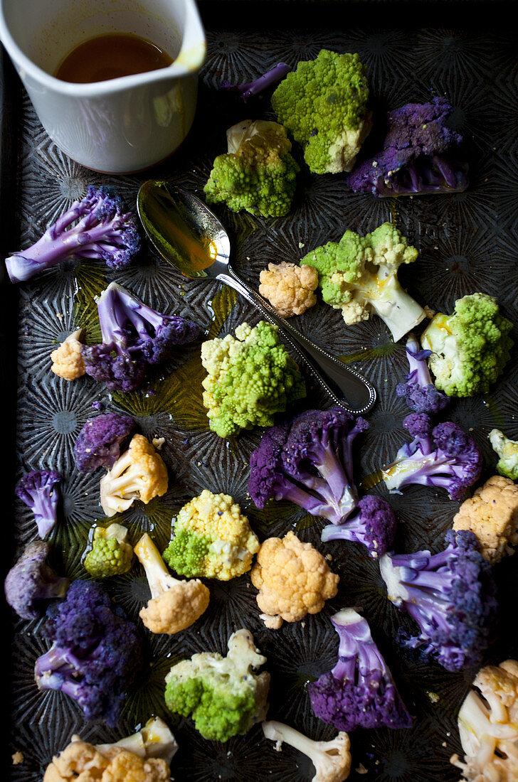 White cauliflower, purple cauliflower and romanesco broccoli with turmeric oil on an antique baking sheet