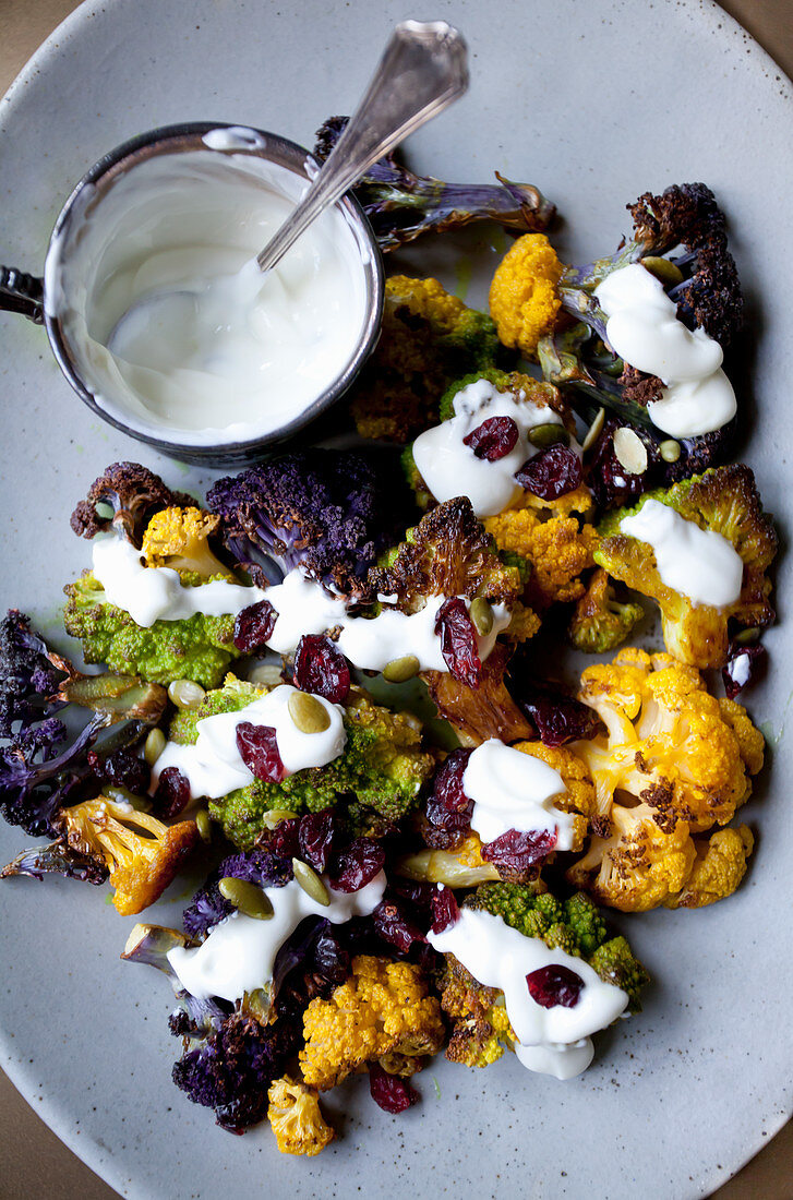 White and purple cauliflower and romanesco broccoli florets roasted in turmeric oil, topped with yogurt sauce with dried cranberries and pumpkin seeds
