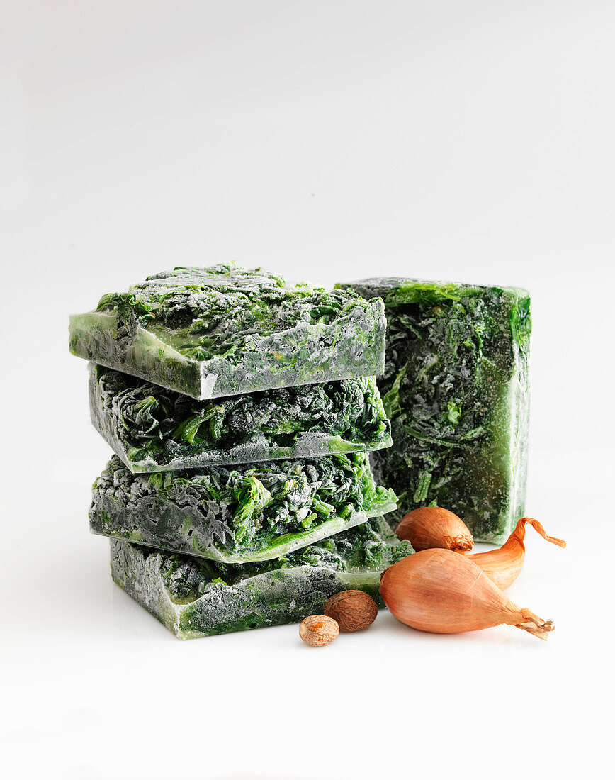 Creamed spinach, frozen in blocks against a white background