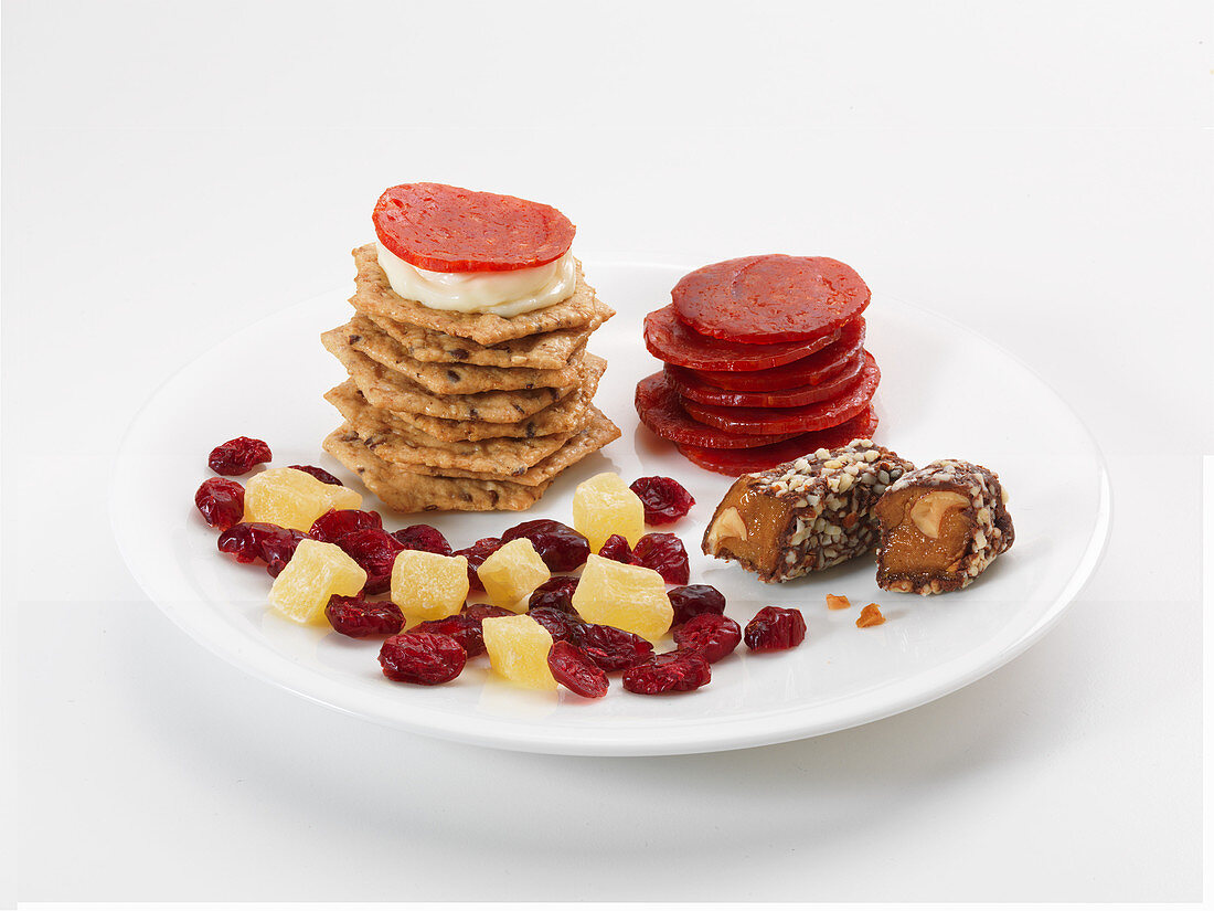 Sweet and savoury snacks on plates: crackers, sausages, dried fruits and sweets