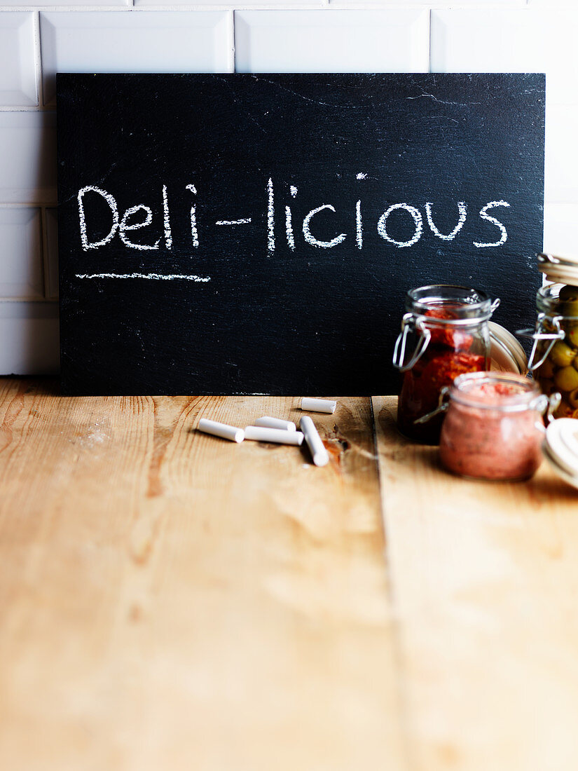 Chalkboard with handwritten 'Deli-licious' and various preserving jars