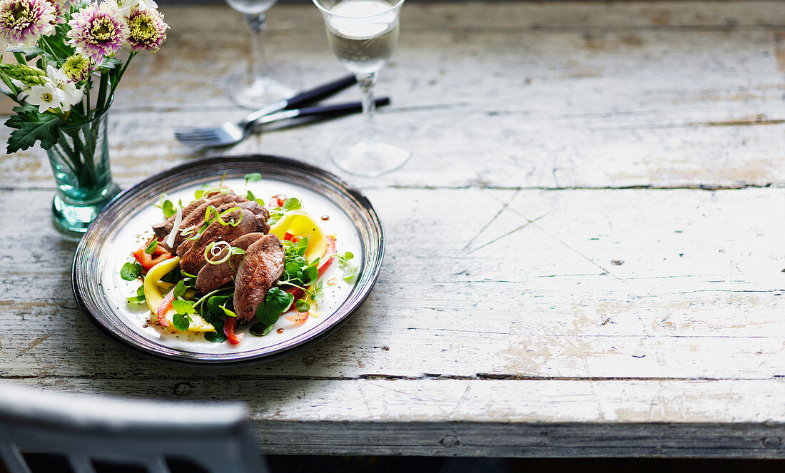 Duck breast on mango and pepper salad with watercress and spring onions