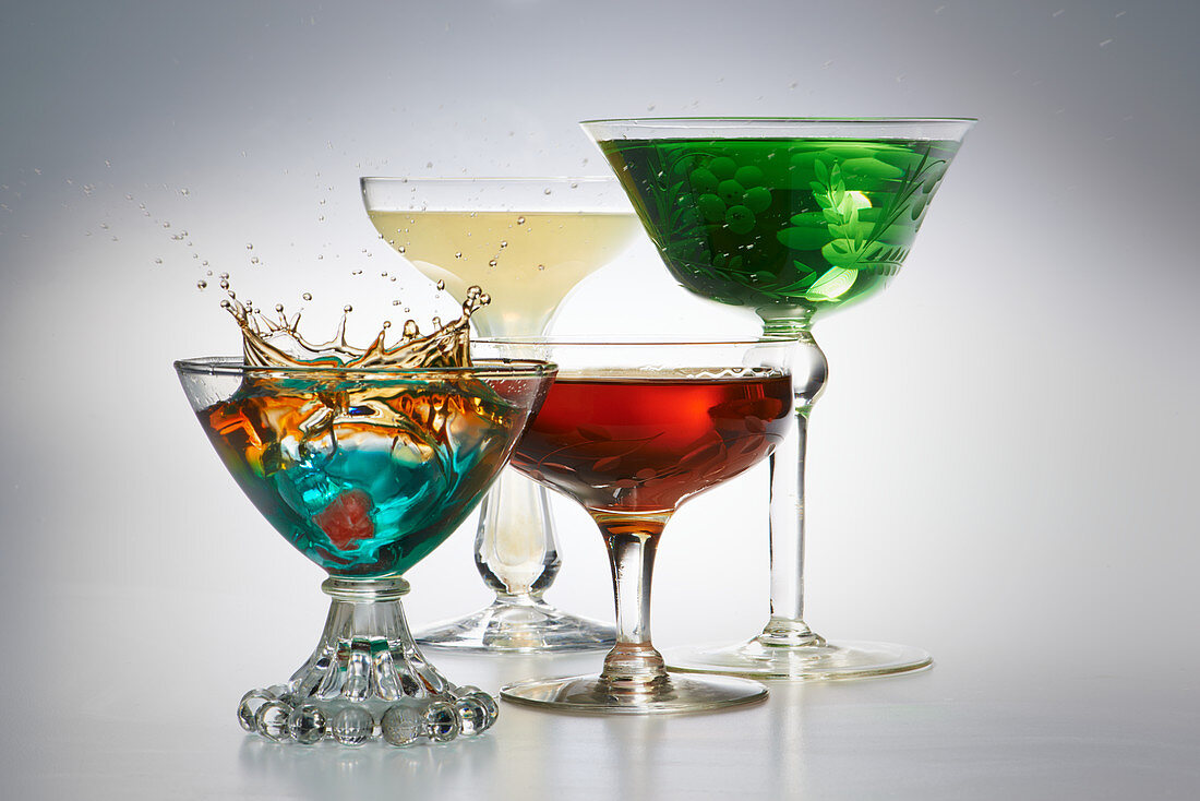 Four different cocktails in glasses against a gray background