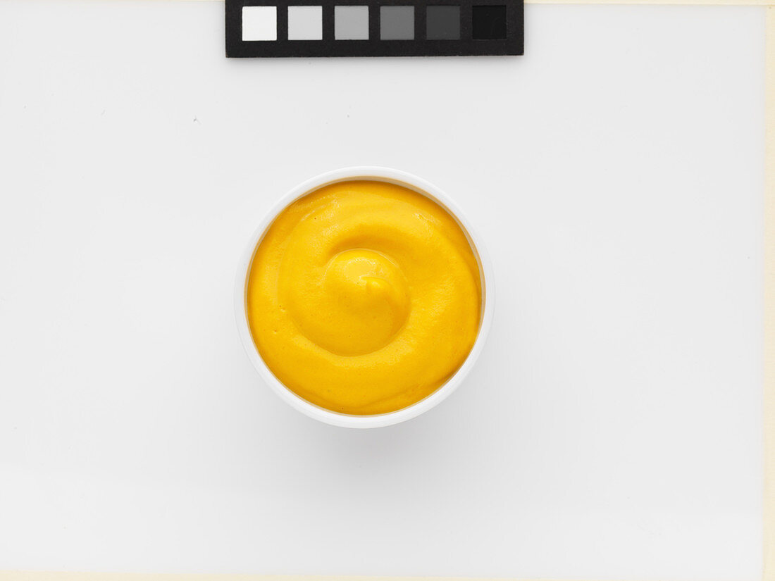 A bowl of mustard against a white background (top view)