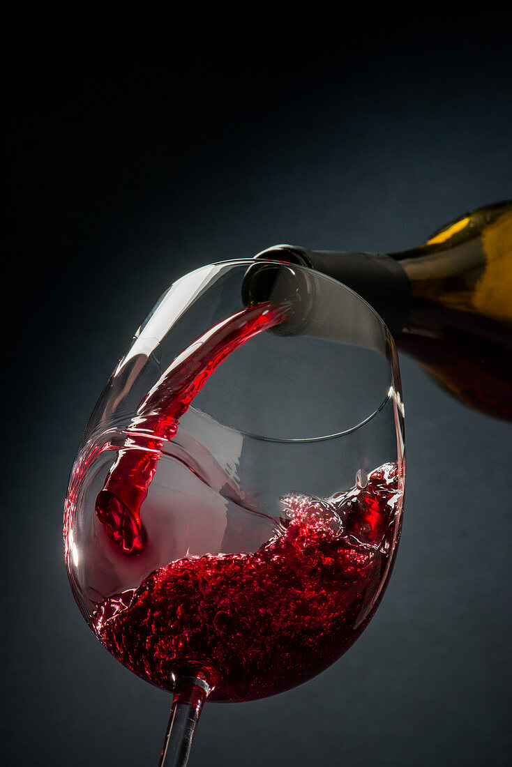 Red wine poured from a bottle into a glass