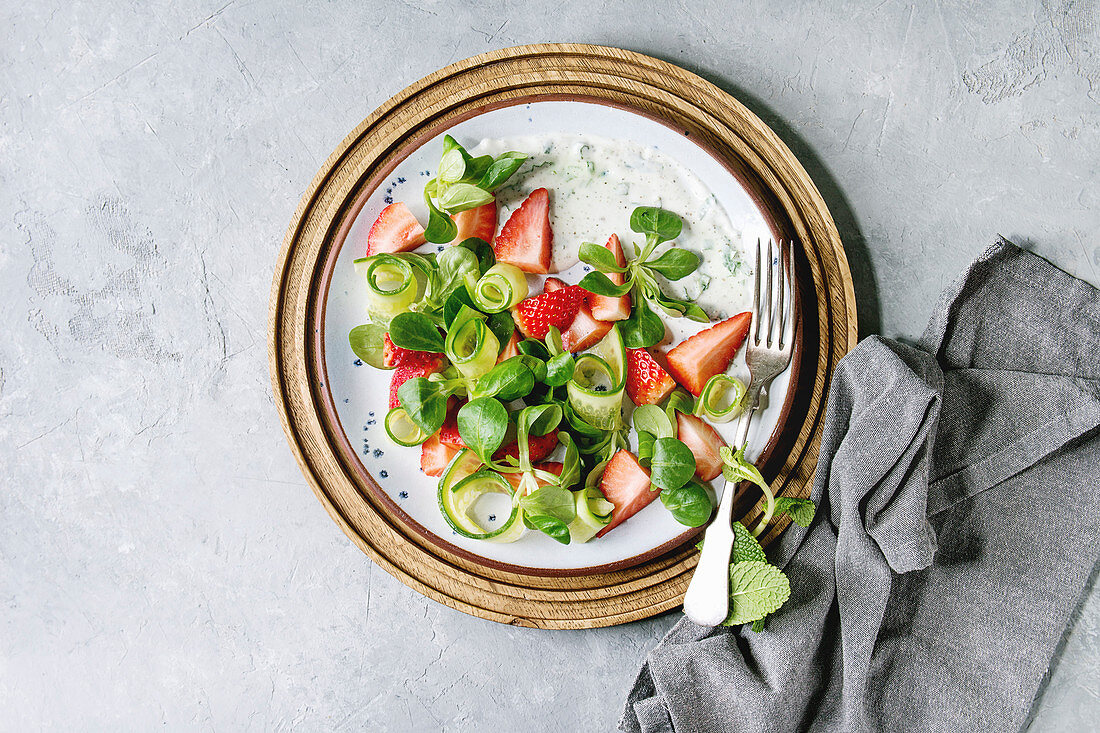 Spring summer diet salad with strawberries, cucumber, green field salad and yogurt mint sauce