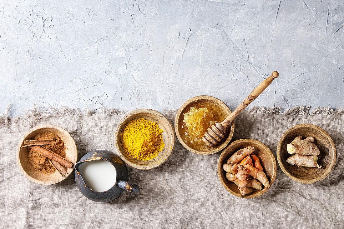 Ingredients for turmeric latte. Ground turmeric, curcuma root, cinnamon, ginger, honeycombs in wooden bowls, jug of milk
