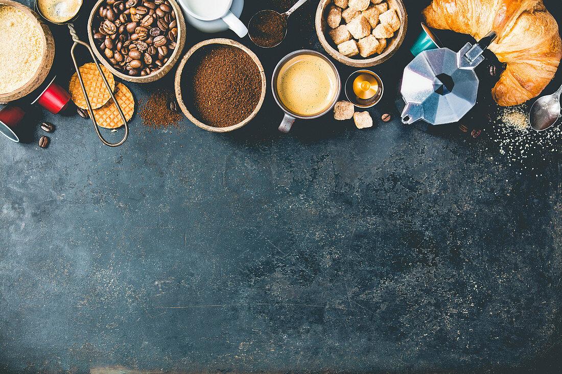 Coffee composition on dark background. Coffee espresso in dark cups, coffee beant, ground coffee, brown sugar, milk, croissants, capsules