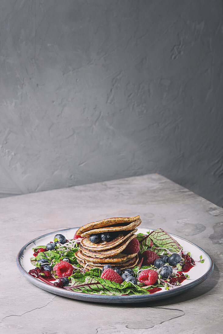 Vegan chickpea pancakes served in plate with green salad young beetroot leaves, sprouts, berries, berry sauce over grey kitchen table
