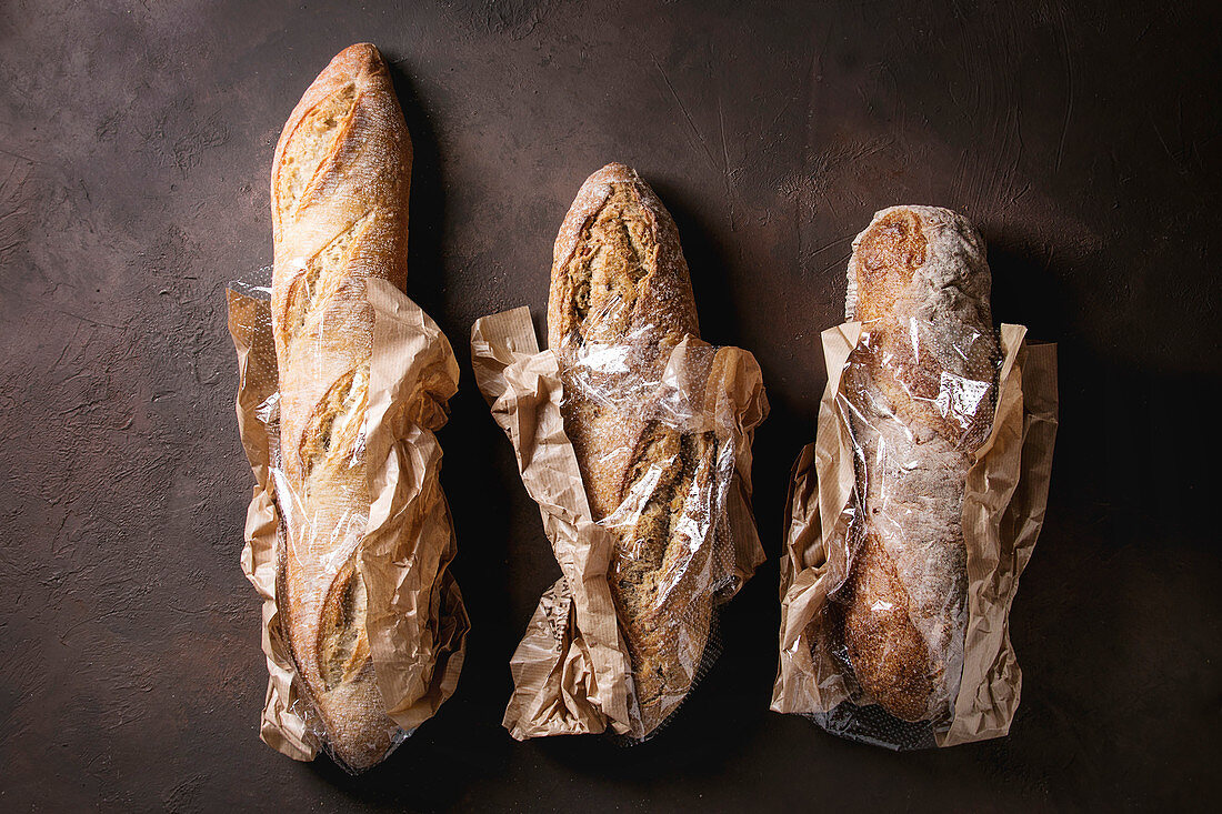 Variety of loafs of fresh baked artisan rye, whole grain and white bread in market paper bag