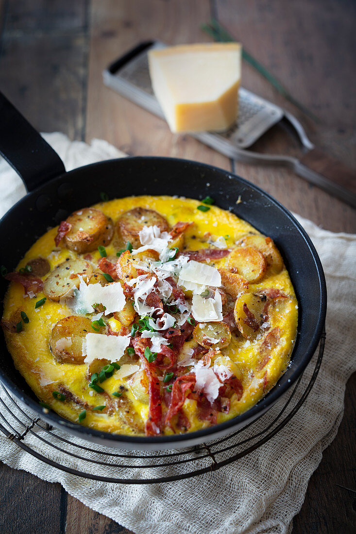 Potato omelette with bacon and parmesan in a pan