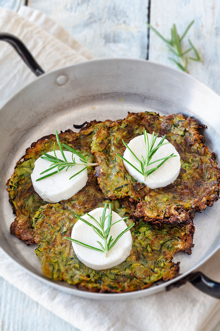Zucchini fritters with goat's cheese in a pan